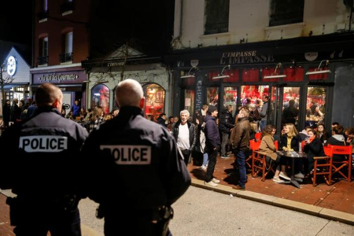 Policemen stand guard while people enjoy dinner and drinks before the French Prime Minister Edouard Philippe's announcement of the shutdown of non-essential commerce and places takes effect in France at midnight, in Le Touquet
