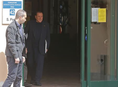 Former Italian Prime Minister Silvio Berlusconi (R) walks as he leaves the Sacred Family Foundation in Cesano Boscone, a small town on the outskirts of Milan May 9, 2014. REUTERS/Stefano Rellandini