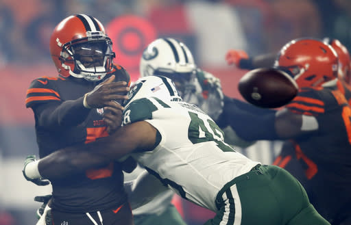 Cleveland Browns quarterback Tyrod Taylor, left, throws an incomplete pass as he is tackled by New York Jets linebacker Jordan Jenkins during the first half of an NFL football game Thursday, Sept. 20, 2018, in Cleveland. (AP Photo/Ron Schwane)