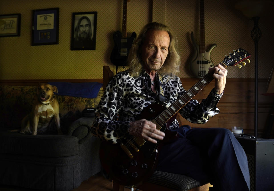 """Paul Raci, an Oscar nominee for best supporting actor for his performance in """"Sound of Metal,"""" plays guitar at his home, Thursday, April 8, 2021, in Burbank, Calif. Raci plays in a Black Sabbath cover band named Hands of Doom. (AP Photo/Chris Pizzello)"""