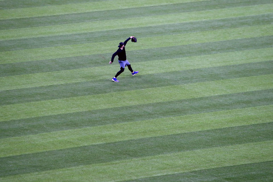 An unidentified player throws in the outfield at Globe Life Field, home of the Texas Rangers baseball team, in Arlington, Texas, Monday, June 1, 2020. The coronavirus pandemic has forced universities, leagues and franchises to evaluate how they might someday welcome back fans. While opinions vary from sport to sport, nation to nation and even state to state, one thing seems clear: Social distancing is very much a sure bet when fans return. (AP Photo/LM Otero)