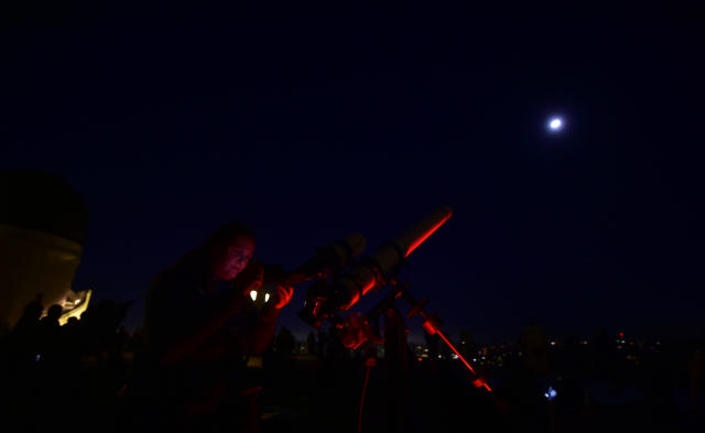 <p>Telescopes are used for a closer view as people attend the lunar eclipse celebration at Griffith Observatory in Los Angeles, Calif., in the early hours of Jan. 31, 2018, to witness the Super Blue Blood Moon, an event not seen since 1866 when three fairly common lunar happenings occur at the same time. (Photo: Frederic J. Brown/AFP/Getty Images) </p>
