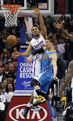 New Orleans Hornets guard Austin Rivers, right, gets a shot blocked by Los Angeles Clippers center Ryan Hollins during the first half of an NBA basketball game in Los Angeles, Monday, Nov. 26, 2012. (AP Photo/Chris Carlson)