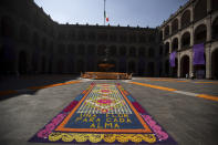 "A patio inside the presidential palace is decorated with the traditional colors of Day of The Dead, with the Spanish message ""A flower for each soul,"" in Mexico City, Saturday, Oct. 31, 2020. The holiday isn't the same in a year so marked by death in a country where more than 90,000 people have died of COVID-19, many cremated rather than buried and with cemeteries forced to close. (AP Photo/Fernando Llano)"