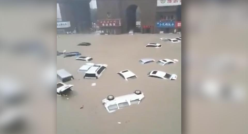 Dozens of vehicles, some overturned, float in a flooded street. Source: Weibo