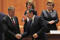 Romania's new President Klaus Iohannis (L) shakes hands with Prime Minister Victor Ponta as he arrives for his swearing-in ceremony in front of the Parliament in Bucharest December 21, 2014. REUTERS/Radu Sigheti