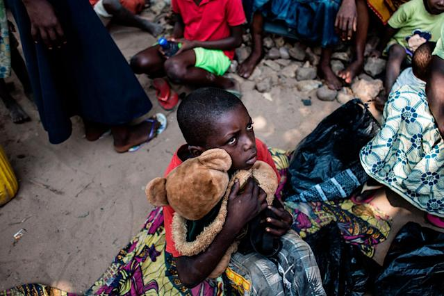 <p>A boy holds his teddy bear as he waits with other Internally Displaced Persons (IDP) for a daily food ration at a camp for IDP's fleeing the conflict in the Kasai Province on June 7, 2017 in Kikwit, Democratic Republic of Congo. (Photo: John Wessel/AFP/Getty Images) </p>