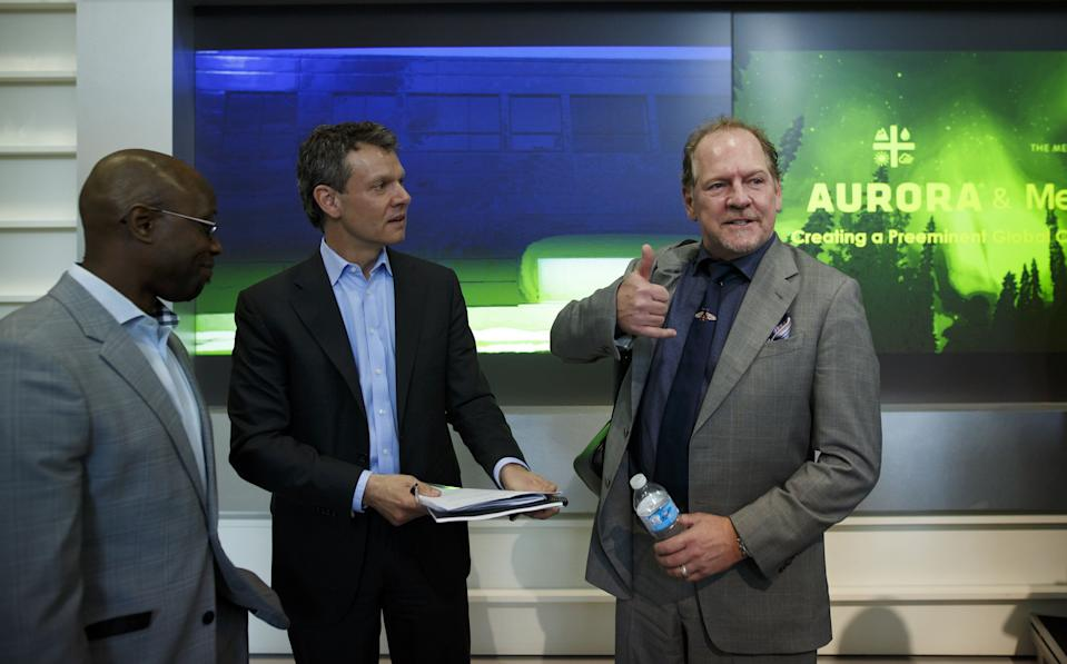 Terry Booth, chief executive officer of Aurora Cannabis Inc., right, gestures while speaking with Cam Battley, chief corporate officer of Aurora Cannabis Inc., center, during a news conference at the Toronto Stock Exchange (TSX) in Toronto, Ontario, Canada, on Monday, May 14, 2018. Aurora Cannabis Inc.agreed to buy rival MedReleaf Corp. for about C$2.9 billion ($2.3 billion) in stock, the companies said Monday in astatement. The deal will create a producer with the capacity to grow 570,000 kilos (1.26 million pounds) a year of cannabis at nine facilities in Canada and two in Denmark. Photographer: Cole Burston/Bloomberg via Getty Images