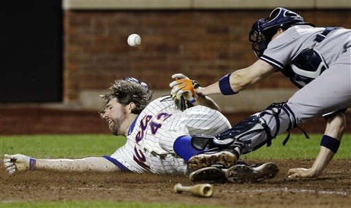 New York Mets' R.A. Dickey (43) is safe sliding home on David Wright's fifth-inning, RBI single during their interleague baseball game against the New York Yankees at Citi Field in New York, Sunday, June 24, 2012. (AP Photo/Kathy Willens)