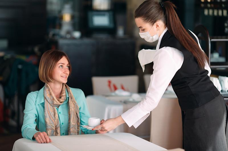 young woman with bob sitting at table in restaurant being served coffee by woman in mask