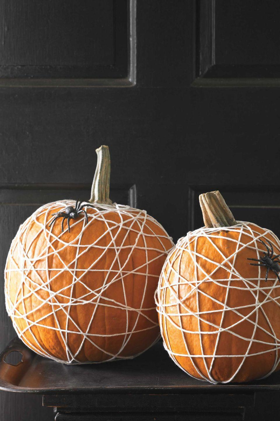 """<p>Cotton kitchen twine and few plastic spiders transform pumpkins from bright and cheery to creepy-crawly in a matter of minutes.</p><p><strong><em><a href=""""https://www.womansday.com/home/crafts-projects/how-to/a5880/halloween-craft-how-to-spider-web-pumpkin-123345/"""" rel=""""nofollow noopener"""" target=""""_blank"""" data-ylk=""""slk:Get the Tangled Web tutorial."""" class=""""link rapid-noclick-resp"""">Get the Tangled Web tutorial.</a></em></strong></p>"""