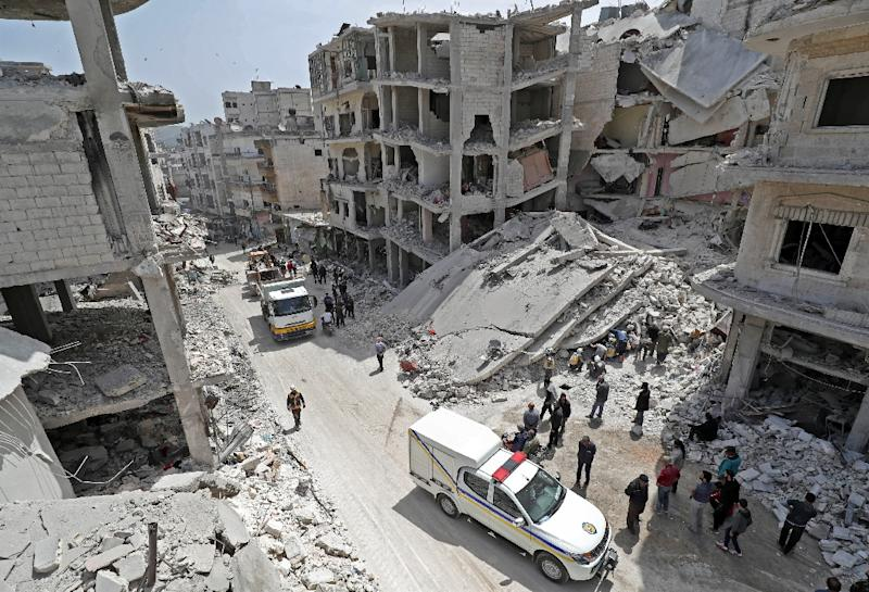 "People watch members of the Syrian Civil Defense, or ""White Helmets,"" search the rubble of a collapsed building following an explosion in the town of Jisr al-Shughur, in the west of the mostly rebel-held Syrian province of Idlib, on April 24, 2019 (AFP Photo/OMAR HAJ KADOUR)"