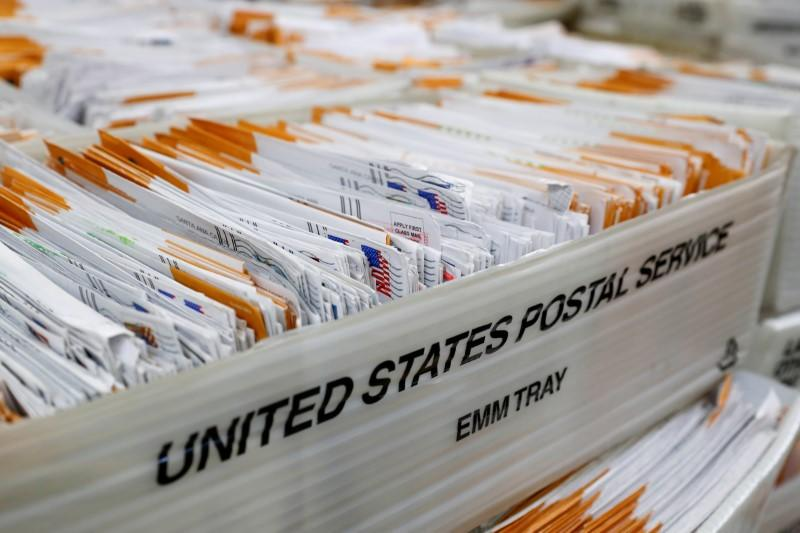 FILE PHOTO: Mail-in ballots for the upcoming congressional election in Orange County wait to be inspected by election workers at the Orange County Registrar of Voters in Santa Ana, California