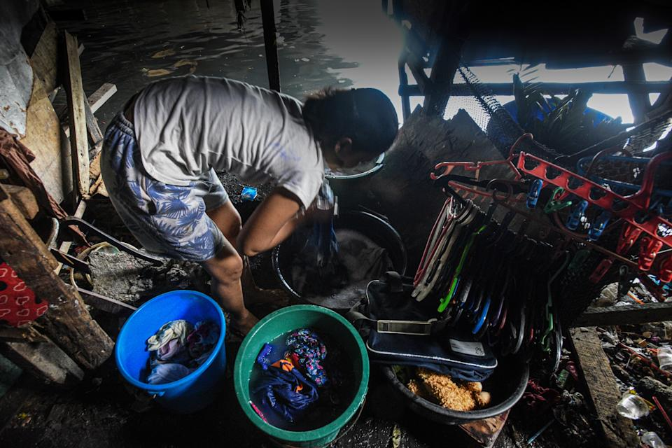 This photo taken on March 18, 2020 shows a mother washing laundry outside her home along the river in Manila. - Asian nations have imposed increasingly heavy measures to fight the outbreak of the COVID-19 coronavirus, the Philippines has ordered half its population of some 110 million to stay home. (Photo by Maria TAN / AFP) / TO GO WITH Health-virus-Philippines-poverty,FOCUS by Joshua Melvin and Ron Lopez (Photo by MARIA TAN/AFP via Getty Images)