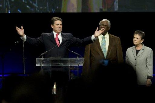 """Texas Gov. Rick Perry (L) speaks alongside Rev. C.L. Jackson, of Houston's Pleasant Grove Missionary Baptist Church (C) and Alice Patterson at the non-denominational prayer and fasting event, entitled """"The Response"""" at Reliant Stadium in Houston, Texas. Perry rallied the faithful for a day of Christian prayer and fasting Saturday asking God to fix America's woes"""