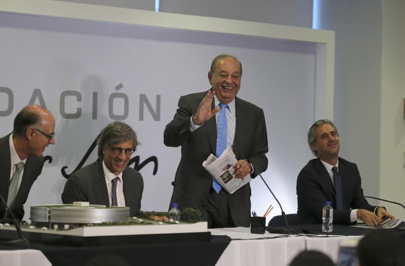 Mexican billionaire Carlos Slim, standing, jokes with journalists at the end of a news conference in Mexico City, Wednesday, Oct. 16, 2019. Slim says he supports President Andrés Manuel López Obrador's objectives. (AP Photo/Fernando Llano)