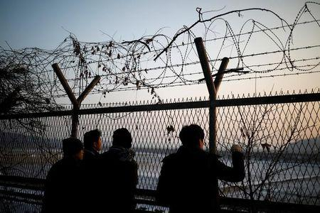 People look toward the north through a barbed-wire fence near the militarized zone separating the two Koreas, in Paju, South Korea, December 21, 2017.  REUTERS/Kim Hong-Ji