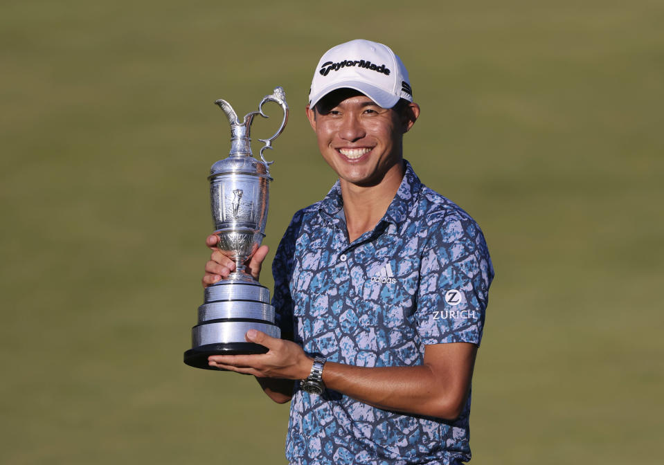 United States' Collin Morikawa holds up the claret jug trophy as he poses for photographers on the 18th green after winning the British Open Golf Championship at Royal St George's golf course Sandwich, England, Sunday, July 18, 2021. (AP Photo/Ian Walton)