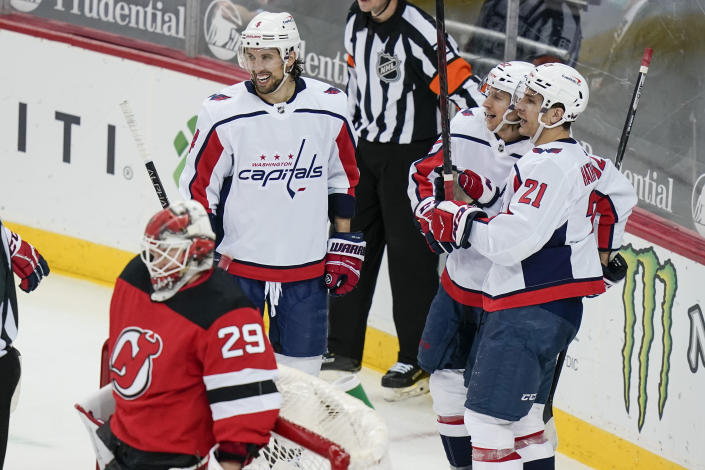 Washington Capitals' Carl Hagelin celebrates with Garnet Hathaway (21) and Brenden Dillon (4) after Hagelin scored a goal during the third period of an NHL hockey game against the New Jersey Devils on Sunday, April 4, 2021, in Newark, N.J. (AP Photo/Frank Franklin II)