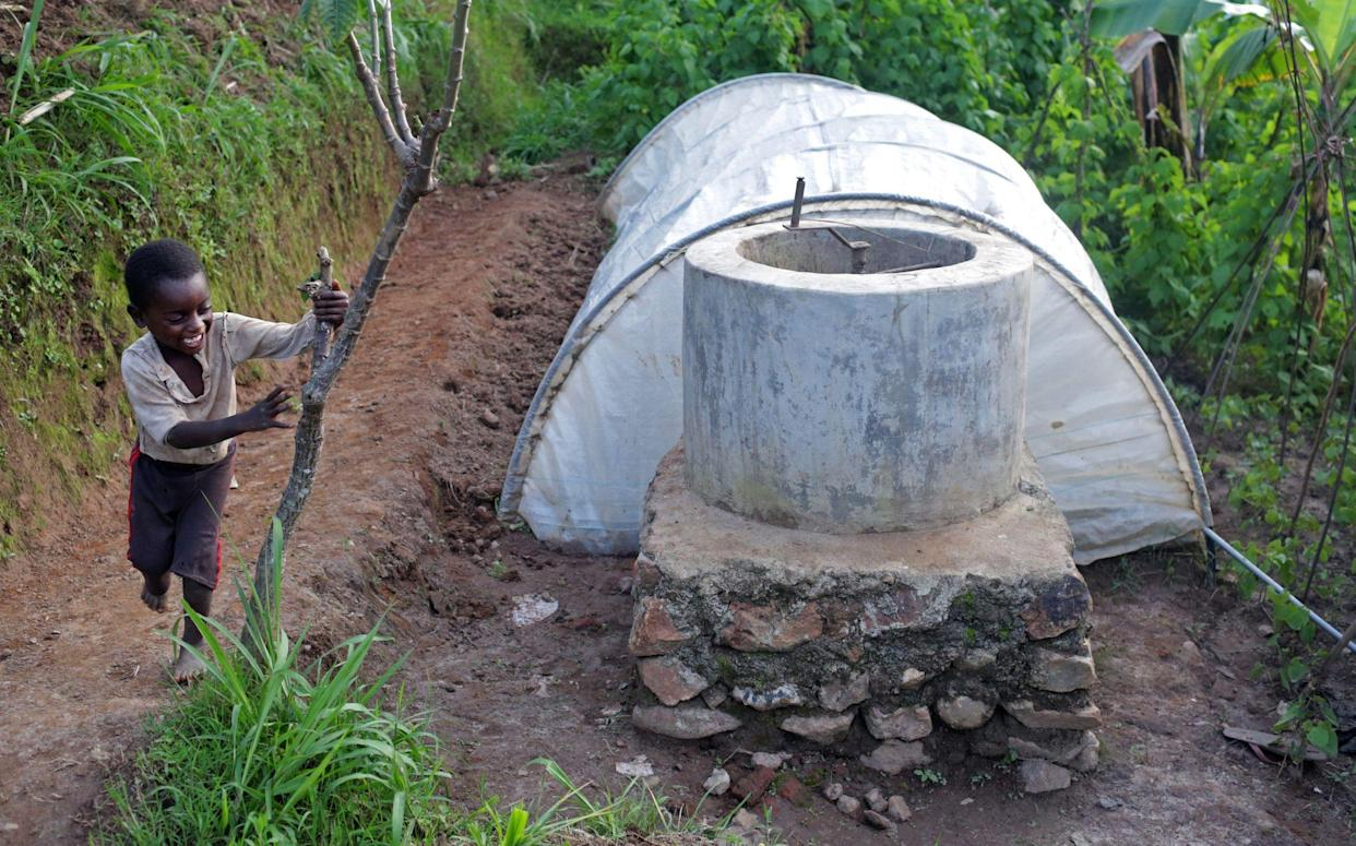 A neighborhood child plays with the Oxfam biogas digester of Jean Claude Niyibizi, 30, and his wife Christine Manirafasha, 26, on November 16, 2017 in their home in Gakenke, Rwanda. Manirafasha says it is easier and quicker to cook with biogas, and that smoke had become a problem while cooking with wood. Her only adjustment, she says, was to remember to turn the gauge to the off position. Having the digester has also allowed her to develop other activities, like a chicken farm and tailoring business. (Photograph by Yana Paskova)