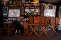 "Debbie Briano, a fourth-generation owner of Mexican restaurant, El Rancho Grande, works in her restaurant next to chairs and tables pushed against the wall on Olvera Street in downtown Los Angeles, Wednesday, Dec. 16, 2020. Briano still decorated her cafe like she normally would at Christmas. She bought poinsettias, put up a real tree, hung tinsel, lights, and strung little snowmen and Santa Claus above her window. ""I had to do that to feel normal,"" she said. ""I' m not going to let COVID take away our Christmas magic."" (AP Photo/Jae C. Hong)"