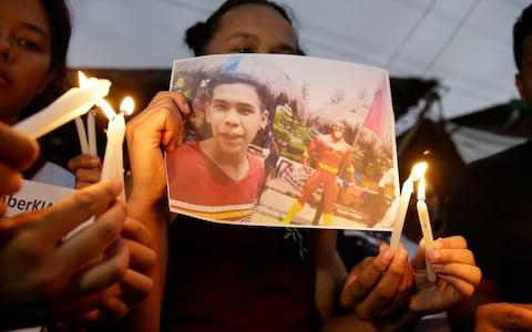 Activists light candles in front of the picture of 17-year-old student Kian Loyd delos Santos in Manila - Credit: AP Photo/Aaron Favila