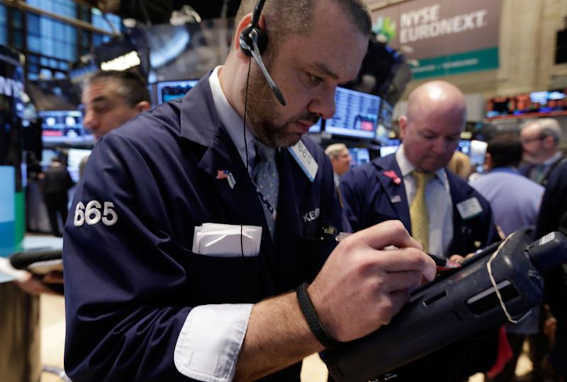 Trader Kevin Lodewick, center, works on the floor of the New York Stock Exchange Wednesday, Jan. 29, 2014. Stocks are lower in early trading as weak earnings from several U.S. companies dented investors' confidence. Worries about emerging markets were also coming back after relief faded over an effort by Turkey to shore up its struggling currency. (AP Photo/Richard Drew)