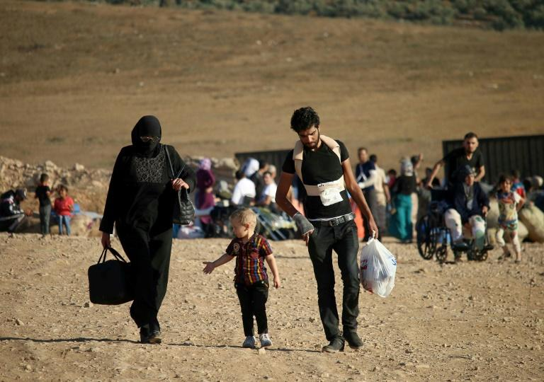 A file picture taken on August 22, 2017 shows Syrians returning home after crossing the Jordanian border near the town of Nasib following a US-Russia ceasefire brokered in the southern provinces of Daraa, Quneitra and Suweida