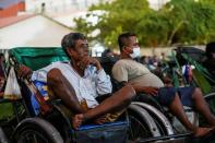 Tricycle drivers attend an outdoor movie screening held by a private organization in Phnom Penh