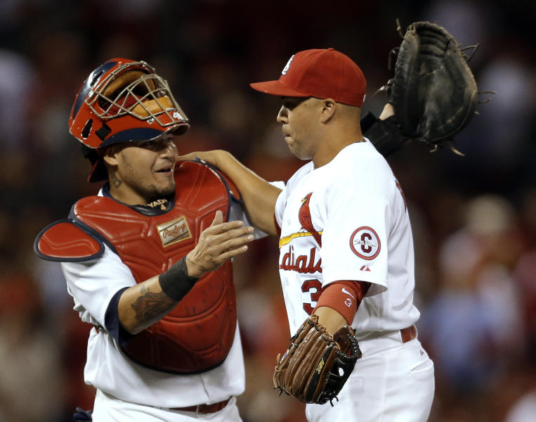 St. Louis Cardinals' Yadier Molina, left, and Carlos Beltran celebrate following the Cardinals' 4-3 victory over the Washington Nationals in a baseball game Monday, Sept. 23, 2013, in St. Louis. (AP Photo/Jeff Roberson)