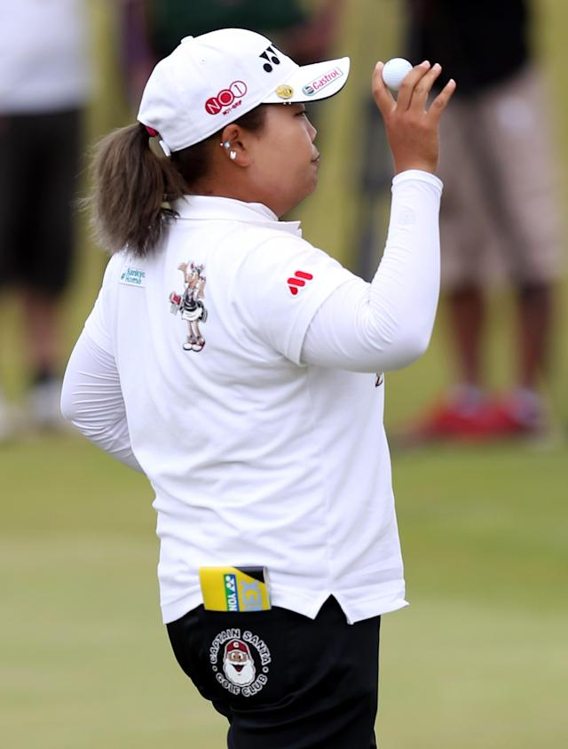 South Korea's Sun Ju Ahn holds up her ball after finishing her round as the leader on the third day of the Women's British Open golf championship at the Royal Birkdale Golf Club, Southport, England, Saturday July 12, 2014. (AP Photo/Scott Heppell)