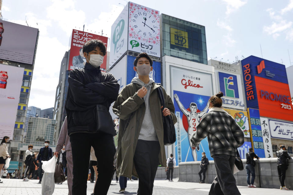 People wearing face masks to help curb the spread of the coronavirus in Osaka, western Japan, Monday, April 5, 2021. Osaka prefecture issued a special warning Wednesday, April 7, 2021 over the rapid upsurge of the coronavirus cases that has put the area's medical systems on the brink of collapse, requesting the cancellation of the Olympic torch relay on public roads. (Juntaro Yokoyama/Kyodo News via AP)