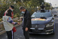 A couple wearing face masks to help curb the spread of the coronavirus gets temperature check before they try out the self-driving ride-hailing services by tech giant Baidu on the outskirts of Beijing on Oct. 15, 2020. Chinese leaders are shifting focus from the coronavirus back to long-term goals of making China a technology leader at this year's highest-profile political event, the meeting of its ceremonial legislature, amid tension with Washington and Europe over trade, Hong Kong and human rights. (AP Photo/Andy Wong)