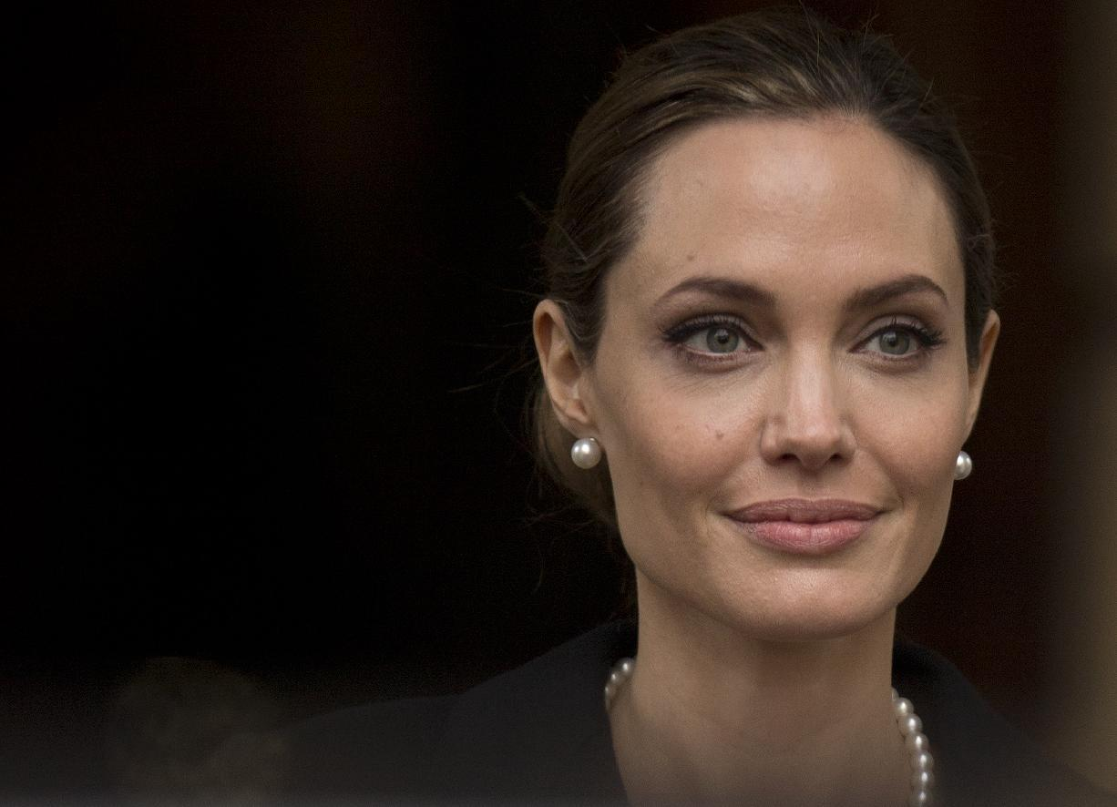 Angelina Jolie looks to the media as she leaves a G8 Foreign Ministers meeting on sexual violence against women in London, Thursday, April, 11, 2013. The ministers are meeting in London as Britain currently holds the G8 Presidency, with the heads of government G8 meeting set for June in Northern Ireland.(AP Photo/Alastair Grant)