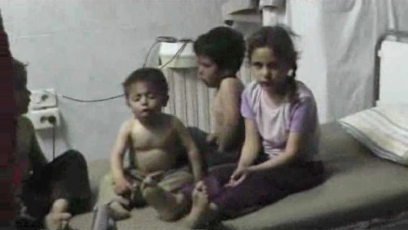 In this Friday, April 11, 2014 image made from amateur video, provided by Shams News Network, a loosely organized anti-Assad group based in and out of Syria that claim not to have any connection to Syrian opposition parties or any other states, and is consistent with independent AP reporting, shows children on a bed at a hospital room in Kfar Zeita, some 200 kilometers (125 miles) north of Damascus, Syria. Syrian government media and rebel forces said Saturday, April 12, 2014 that poison gas had been used in the village on Friday, injuring scores of people, while blaming each other for the attack. (AP Photo/Shams News Network)