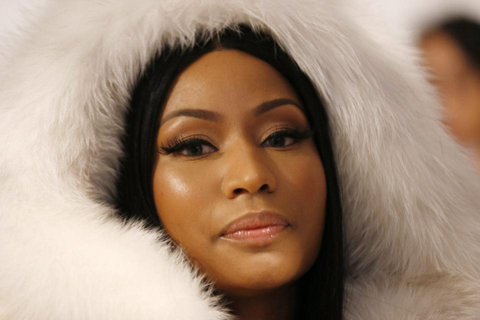 Nicki Minaj, close up of her face, we can see a white fur hood around her head, she has pursed lips