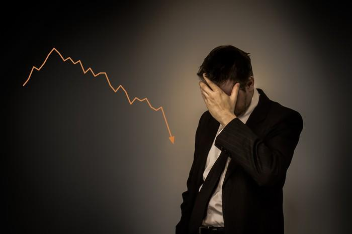 Man in suit with hand over his face standing next to a chart that's trending downward.