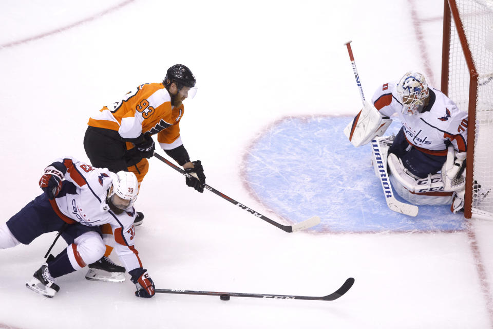 Washington Capitals defenseman Radko Gudas (33) stops a puck in front of Philadelphia Flyers right wing Jakub Voracek (93) at Washington Capitals goaltender Braden Holtby (70) in the net during the second period of an NHL hockey playoff game Thursday, Aug. 6, 2020, in Toronto. (Cole Burston/The Canadian Press via AP)