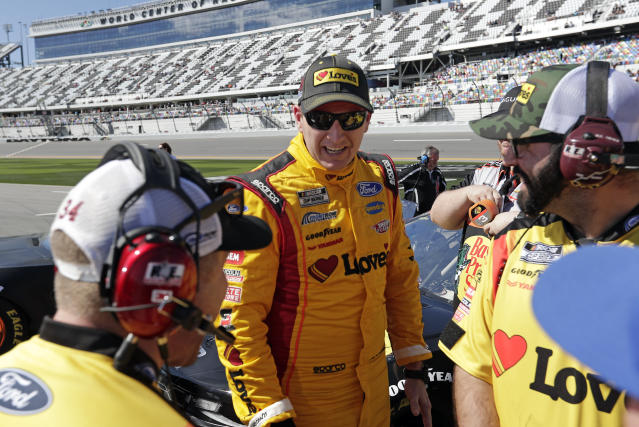 Michael McDowell, center, talks with crew members on pit road during NASCAR auto race qualifying at Daytona International Speedway, Sunday, Feb. 9, 2020, in Daytona Beach, Fla. (AP Photo/John Raoux)