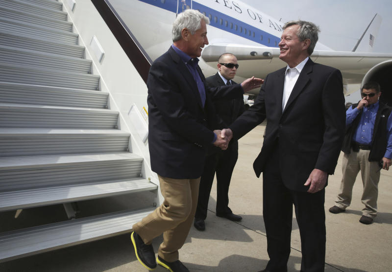 U.S. Secretary of Defense Chuck Hagel, left, is welcomed by U.S. Ambassador to China Max Baucus upon his arrival at Qingdao International Airport in Qingdao, China, Monday, April 7, 2014. Hagel is currently on his fourth trip to Asian nations since taking office. (AP Photo/Alex Wong, Pool)