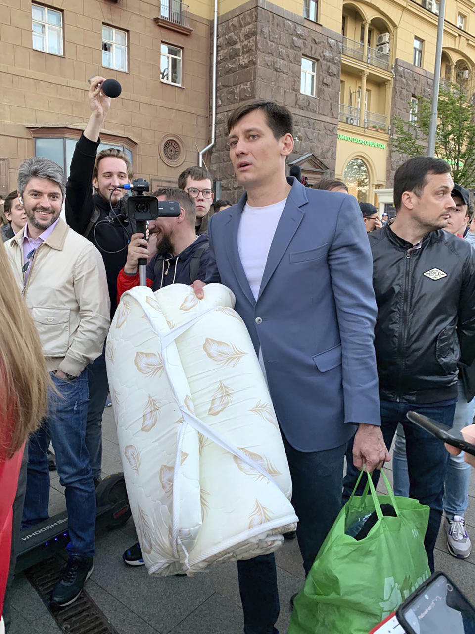 Dmitry Gudkov, center, a former Russian lawmaker who has aspired to run again for a parliament seat, is surrounded by people after being released in case of an expiration of 48 hours of detention in Moscow, Russia, Thursday, June 3, 2021. Police have released a well-known Russian opposition politician from custody after holding him for two days. Gudkov was detained by police at his country house on Tuesday in connection with an investigation into money owed to the city for rental of an office space. Gudkov's attorney, Mikhail Biryukov, said it was not clear whether the Thursday release of Gudkov meant the investigation was still active. (AP Photo/Vladimir Kondrashov)