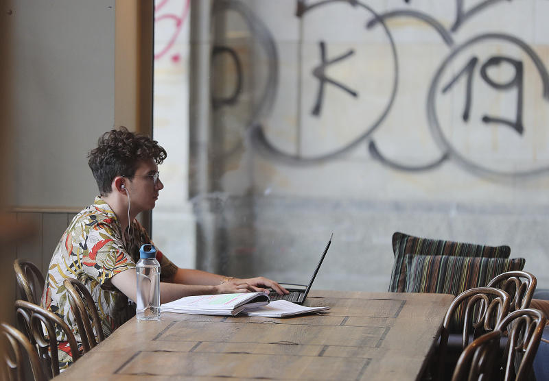 A Polish man works on a laptop in a cafe in Warsaw, Poland, Thursday, Aug. 1, 2019.Poland on Thursday scrapped its personal income tax for young employees earning less than dollars 22,000 a year, as part of a drive to reverse a brain drain and demographic decline that's dimming the prospects of a country that is otherwise experiencing strong economic growth.(AP Photo/Czarek Sokolowski)