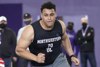 FILE - Northwestern offensive lineman Rashawn Slater participates in the school's Pro Day football workout for NFL scouts in Evanston, Ill., in this Tuesday, March 9, 2021, file photo. Slater is as possible first round pick in the NFL Draft, April 29-May 1, 2021, in Cleveland. (AP Photo/Charles Rex Arbogast, File)