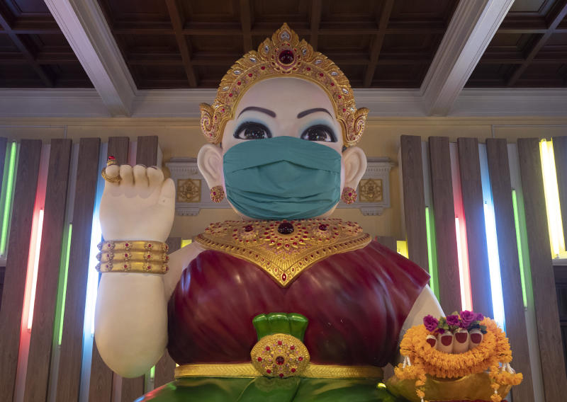 A giant statue of the Thai spiritual Nagkwank is dressed with a face mask at the Siam museum in Bangkok, Thailand, Friday, May 29, 2020. Nagkwank is a benevolent spirit who is deemed to bring luck and prosperity. She is the patron deity of all merchants and salesmen and can be seen in very many business establishments in Thailand. Thai authorities allowed museum and other businesses to reopen, selectively easing restrictions against the coronavirus. (AP Photo/Sakchai Lalit)