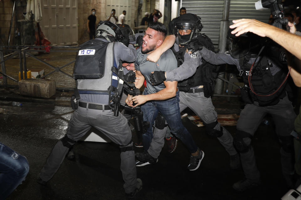 Israeli police officers clash with Palestinian protesters near Damascus Gate just outside Jerusalem's Old City, Sunday, May 9, 2021. (AP Photo/Ariel Schalit)