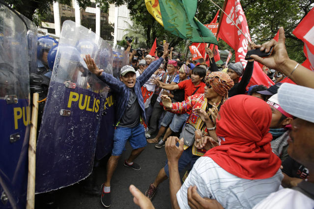 <p>A protester tries to block police from advancing to others after they briefly scuffle with police during a rally near the U.S. Embassy in Manila to protest this weekend's visit of President Donald Trump on Saturday, Nov. 11, 2017 in Manila, Philippines. (Photo: Aaron Favila/AP) </p>