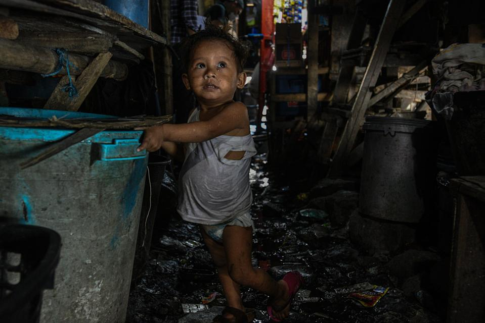 This photo taken on March 18, 2020 shows a child walking along a muddy path near his home in Manila. - Asian nations have imposed increasingly heavy measures to fight the outbreak of the COVID-19 coronavirus, the Philippines has ordered half its population of some 110 million to stay home. (Photo by Maria TAN / AFP) / TO GO WITH Health-virus-Philippines-poverty,FOCUS by Joshua Melvin and Ron Lopez (Photo by MARIA TAN/AFP via Getty Images)