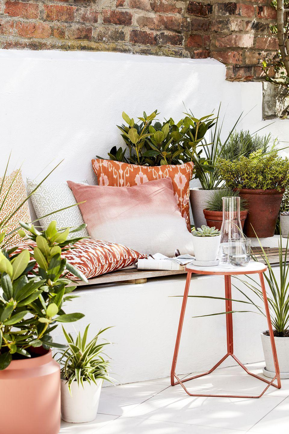 <p>Turn any ol' ledge into an ultra-cozy seating nook. Outfit the wide railing or garden wall with colorful pillows and potted plants, and then pull up a small side table. </p>