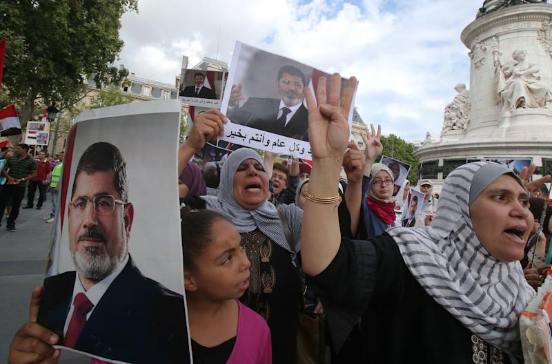 Egyptian supporters of ousted Egyptian President Mohammed Morsi, living in France, protest in Paris, Sunday, Aug. 18, 2013. The supporters carry pictures of the ousted president. (AP Photo/Michel Euler)