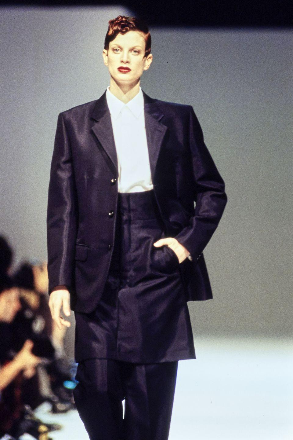 """<p>Cited as an unconventional beauty, McMenamy was nonetheless celebrated for her androgyny. She thankfully didn't heed the advice of model agent Eileen Ford, who encouraged her to <a href=""""https://www.crfashionbook.com/celebrity/a25562079/remember-when-kristen-mcmenamy-eyebrows-birthday/"""" rel=""""nofollow noopener"""" target=""""_blank"""" data-ylk=""""slk:get plastic surgery"""" class=""""link rapid-noclick-resp"""">get plastic surgery</a>. From labels like Chanel, Versace, and Comme des Garçons to photographers like Steven Meisel and Juergen Teller, the fashion industry embraced the Pennsylvania native's uniqueness. </p>"""